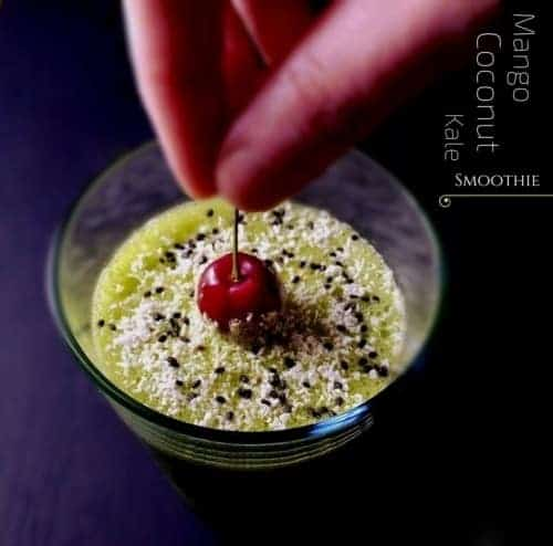 Mango Coconut Kale Smoothie decorated with chia seeds, coconut flakes and some cherry