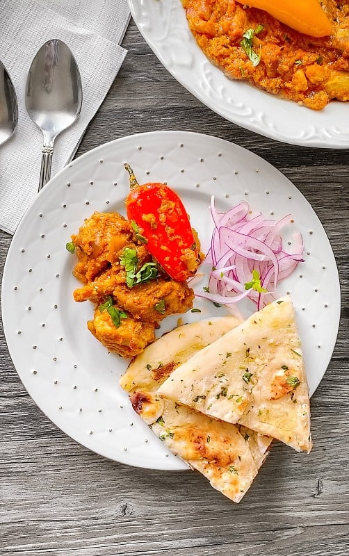 Achari Chicken in a plate with naan and pickled onion