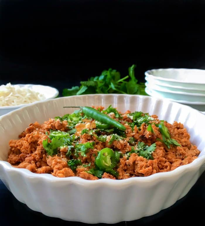 Hyderabadi Dum ka Keema in a bowl with plates around it