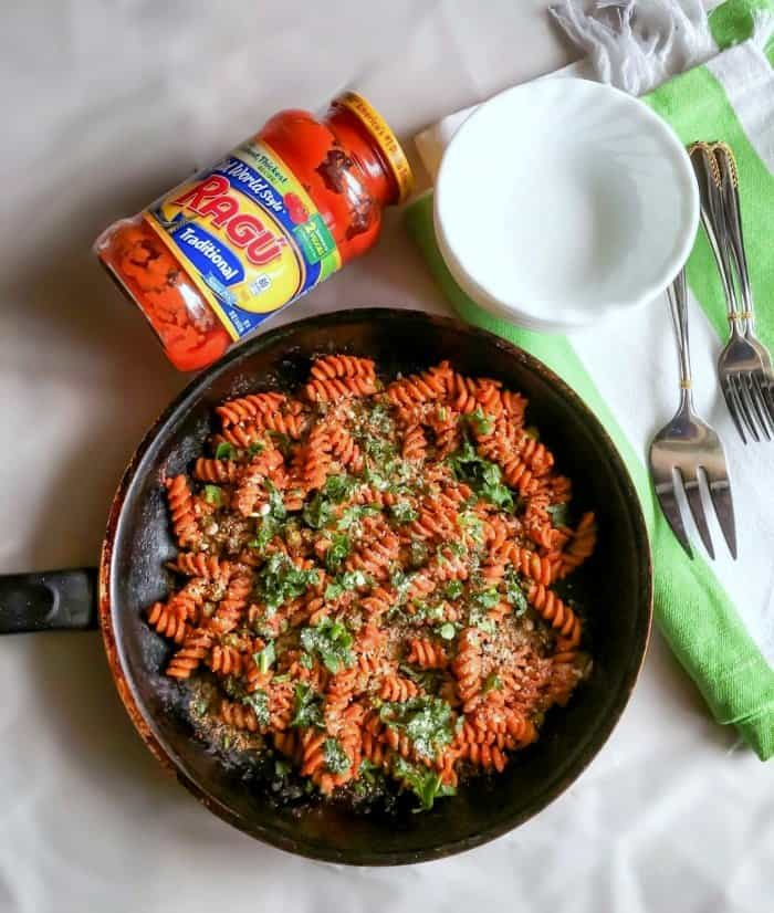 Tomato Peas Pasta in a skillet pan over a white table.