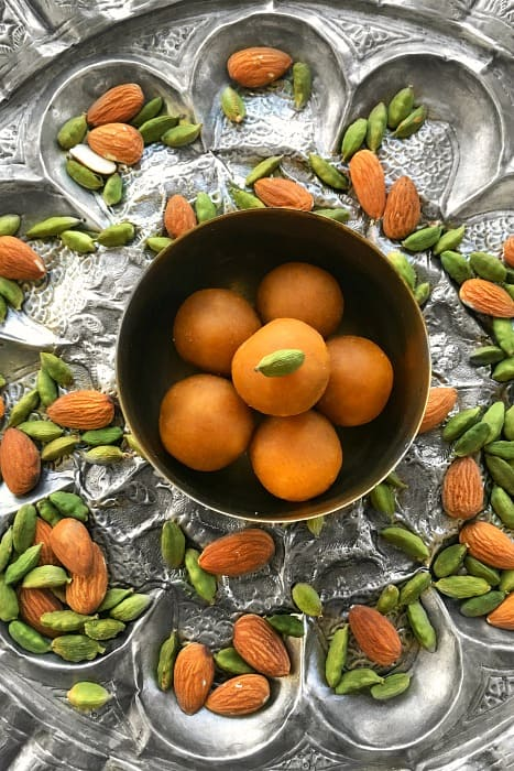 Microwave Besan Ladoo on a large silver ornate plate with almonds and cardamom pods