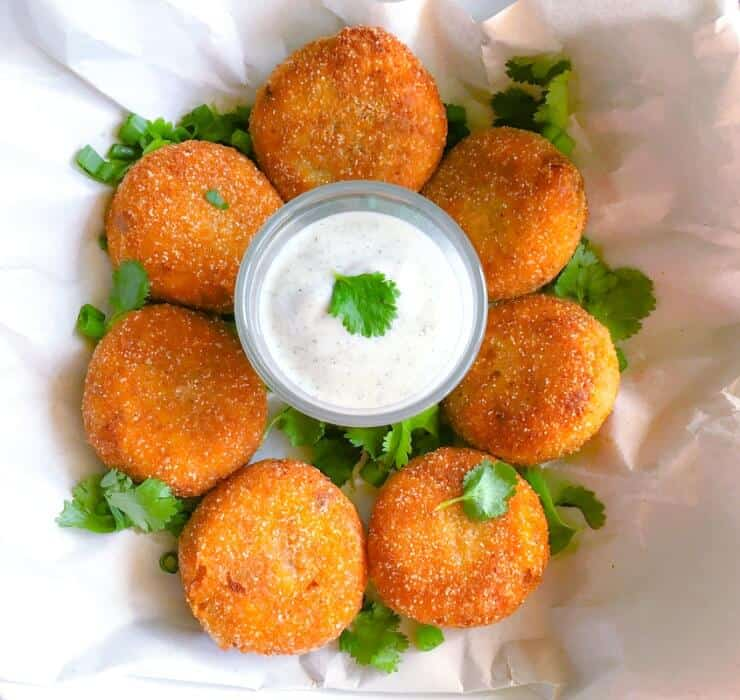 bengali style fish croquette with yogurt sauce, chopped cilantro on a crumbled paper.
