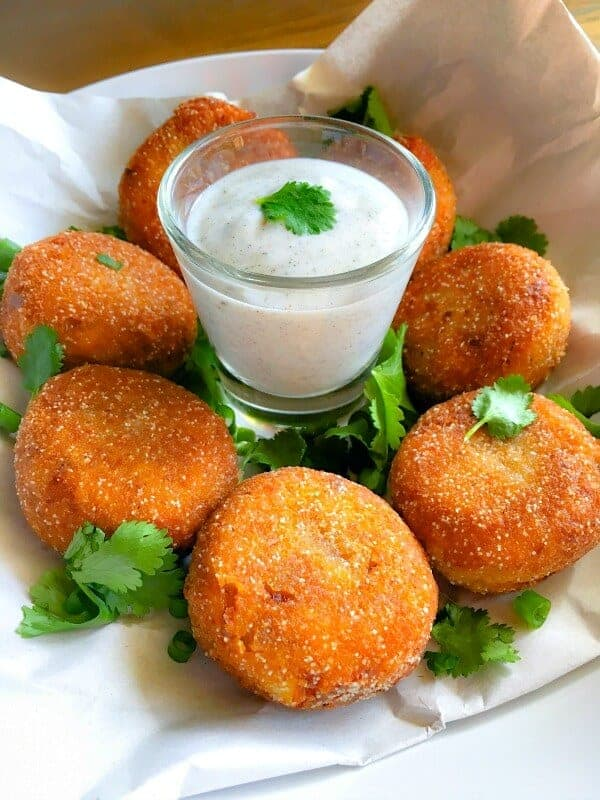 bengali fish croquette with yogurt sauce and chopped cilantro