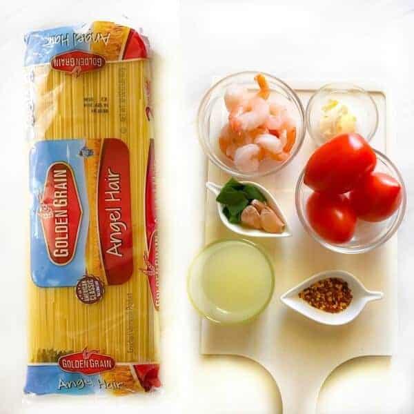how to make shrimp pasta recipe ingredients on a white background. Ingredients are pasta, shrimp, basil, tomato, etc