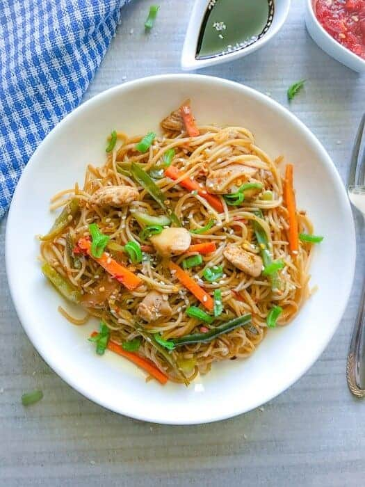 spicy chow mein or lo mein on a white plate with sauces around it