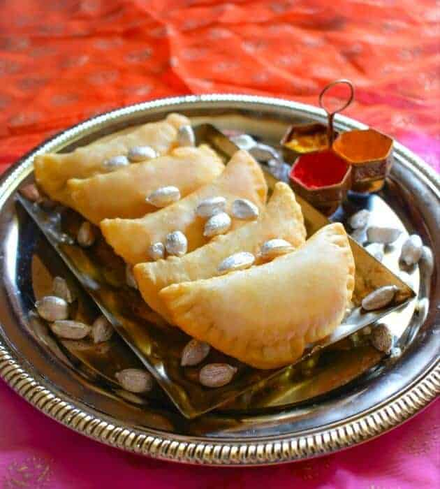 Gujiya or Karanji on a metal plate with cardamoms