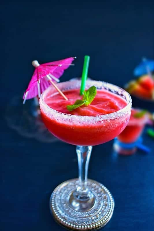 watermelon vodka slushie in a tall glass with umbrella