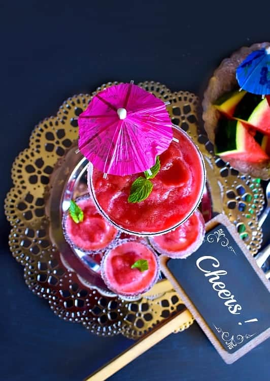 Watermelon Vodka Slushie in 3 glasses with cocktail umbrellas