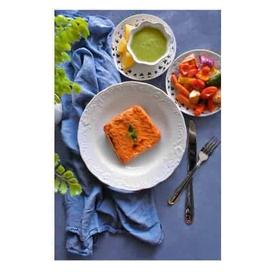 tandoori salmon on a white plate with vegetables on side