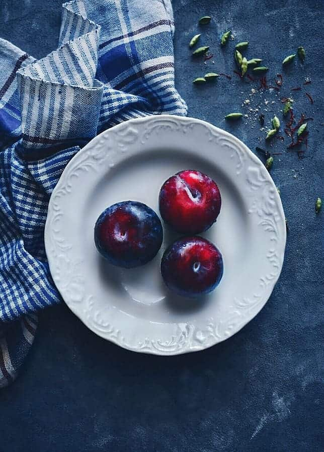 plums in a white plate with check napkin