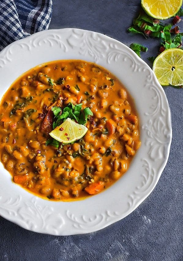 coconut black eyed peas in a white boal with sliced lemons and chopped cilantro
