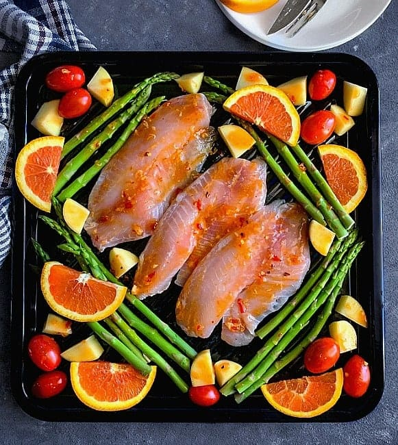 Adding the citrus glaze on tilapia fish, chopped vegetables arranged on sheet pan. Ready for baking..
