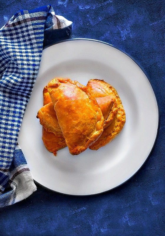 indian lamb curry puffs in a white plate and blue napkin