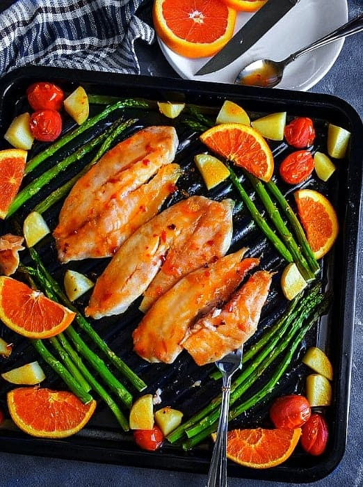 sheet pan orange ginger glazed tilapia fish with vegetables on a black oven tray