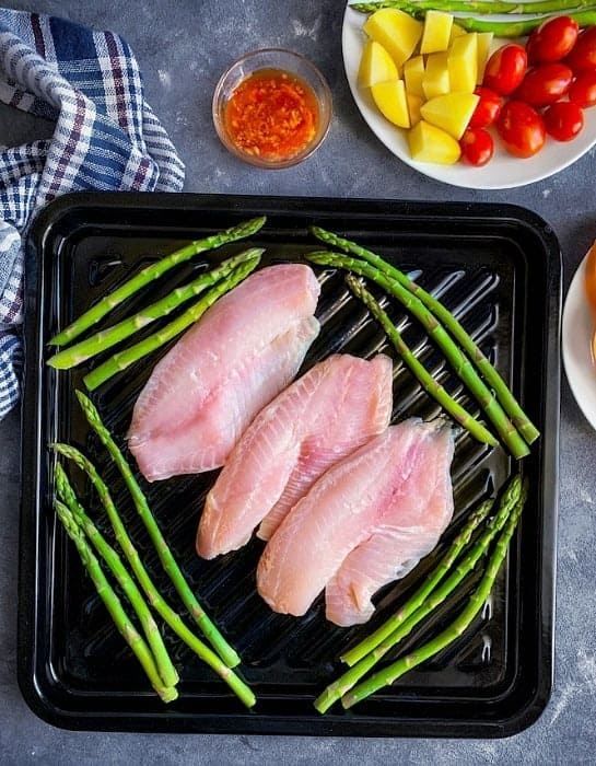 Tilapia fish fillet and asparagus on a sheet pan.