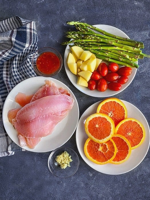 Ingredients for sheet pan orange ginger tilapia recipe. Includes cut oranges, raw tilapia fish fillet, mixed vegetables, orange and ginger marinade