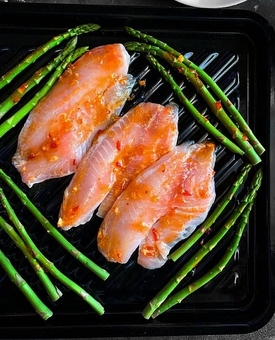 Orange and ginger mixed with spicy sweet sauce and glazed on tilapia fish with asparagus on a black sheet pan