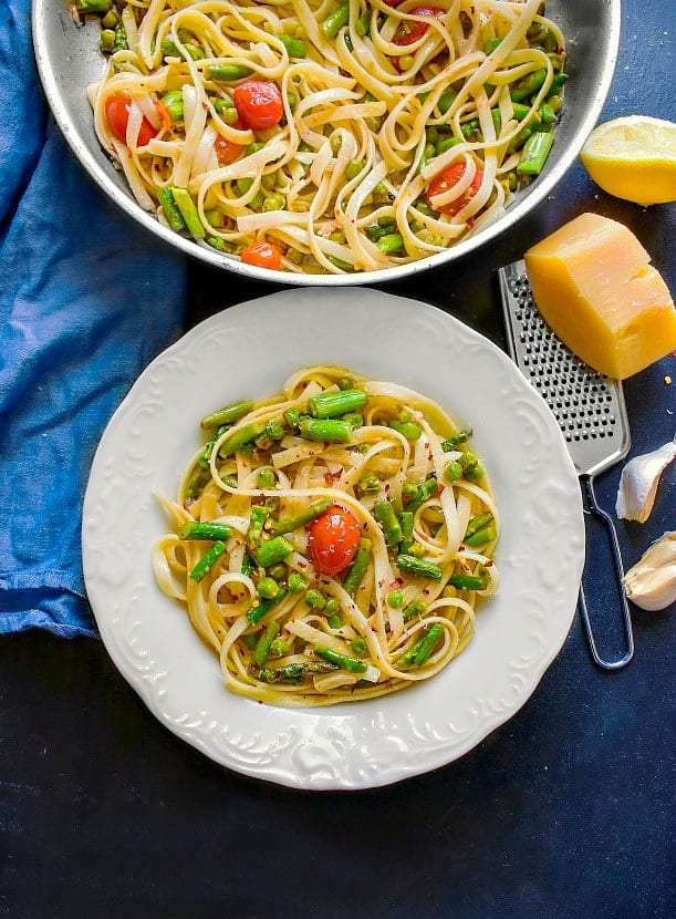 Lemon Asparagus Pasta with Peas and Tomatoes recipe on a white plate and black table