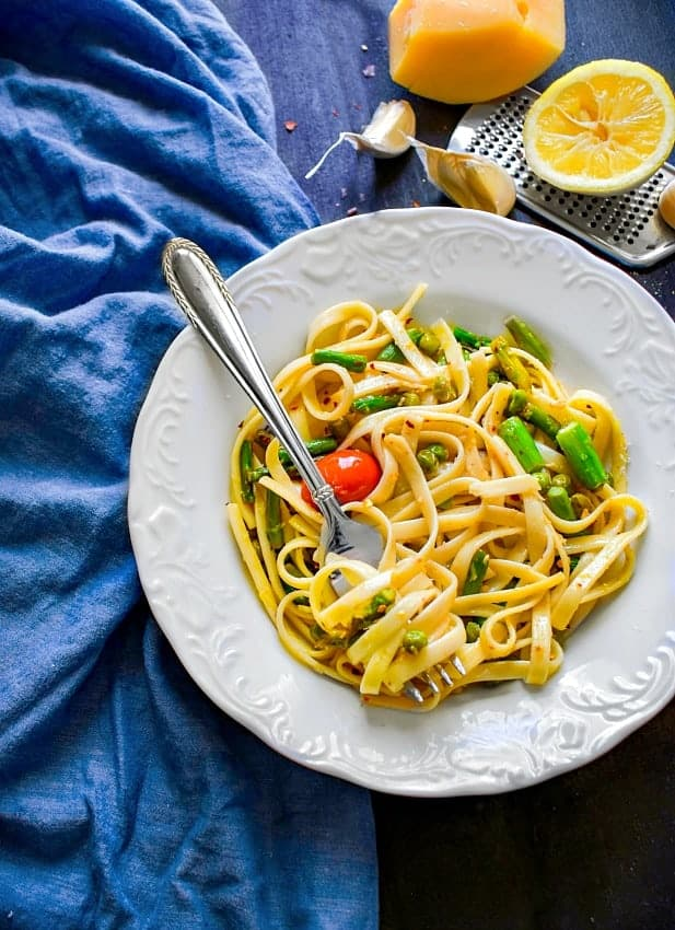 Lemon Asparagus Pasta with Peas in a white plate and blue napkin