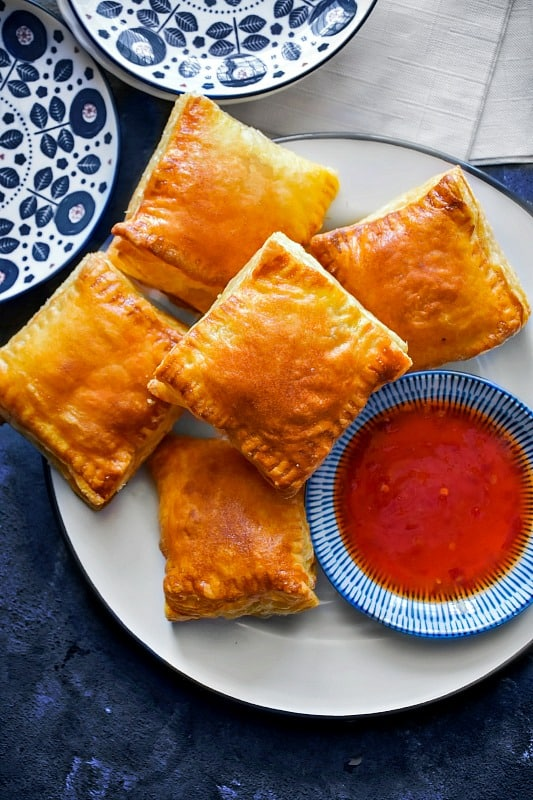 Indian Chicken Puffs on a white plate with sauce.