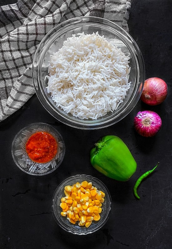 sweet corn fried rice ingredients on a black background