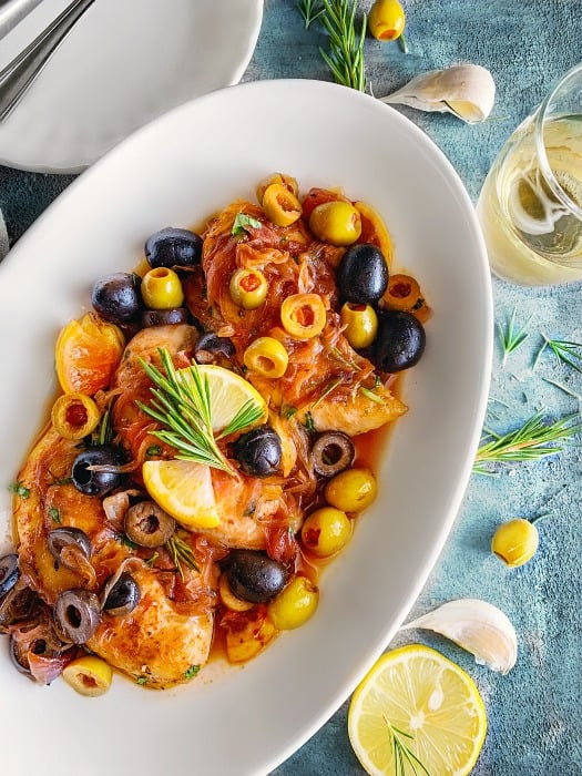 Mediterranean Chicken Recipe on a white plate with olives, onion and lemons