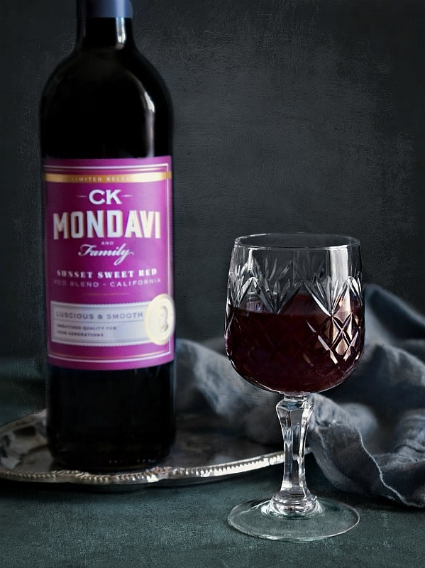 ck mondavi and family red wine in a glass along with bottle on a tray